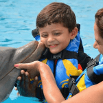 Young boy Getting Dolphin Kiss Mexico